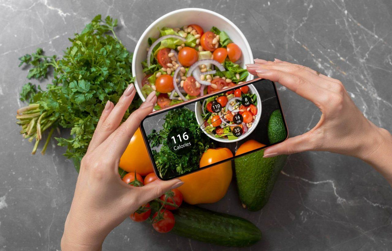 Female using dieting app on a smartphone to track nutrition facts and calories in her food