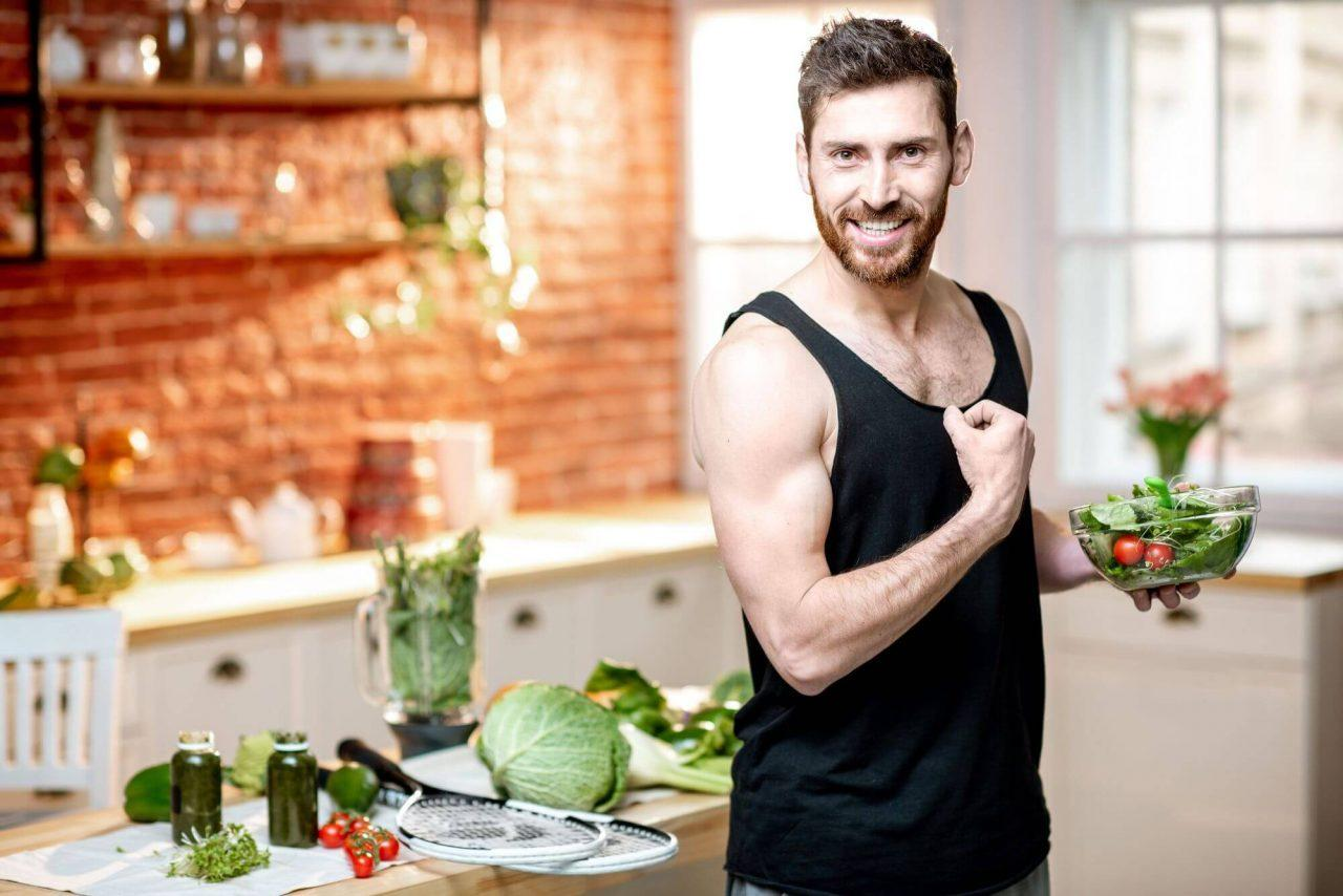 A handsome sports man showing muscles, eating healthy vegetarian salad on the kitchen at home