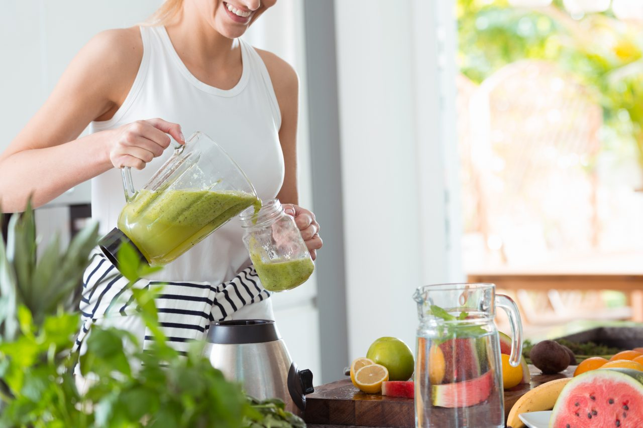 Happy woman on vegan diet, pouring green smoothie cocktail from mixer into glass in kitchen