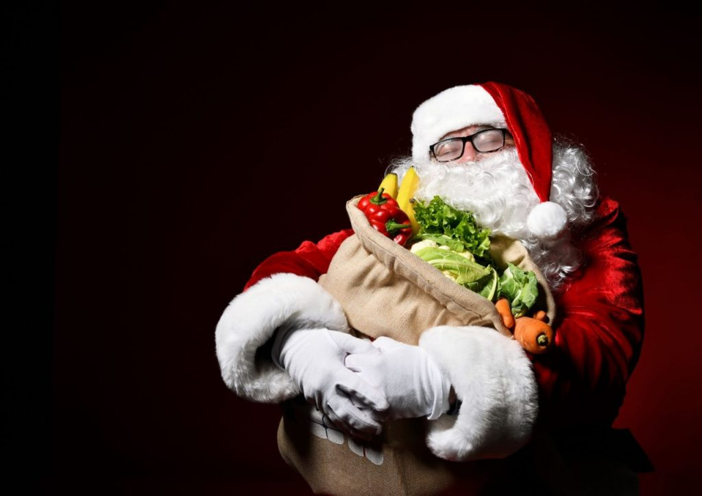 Jolly Santa Claus is holding a big bag full of fruits and vegetables