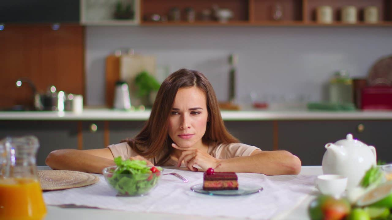 Smiling woman making decision between salad and cake on kitchen