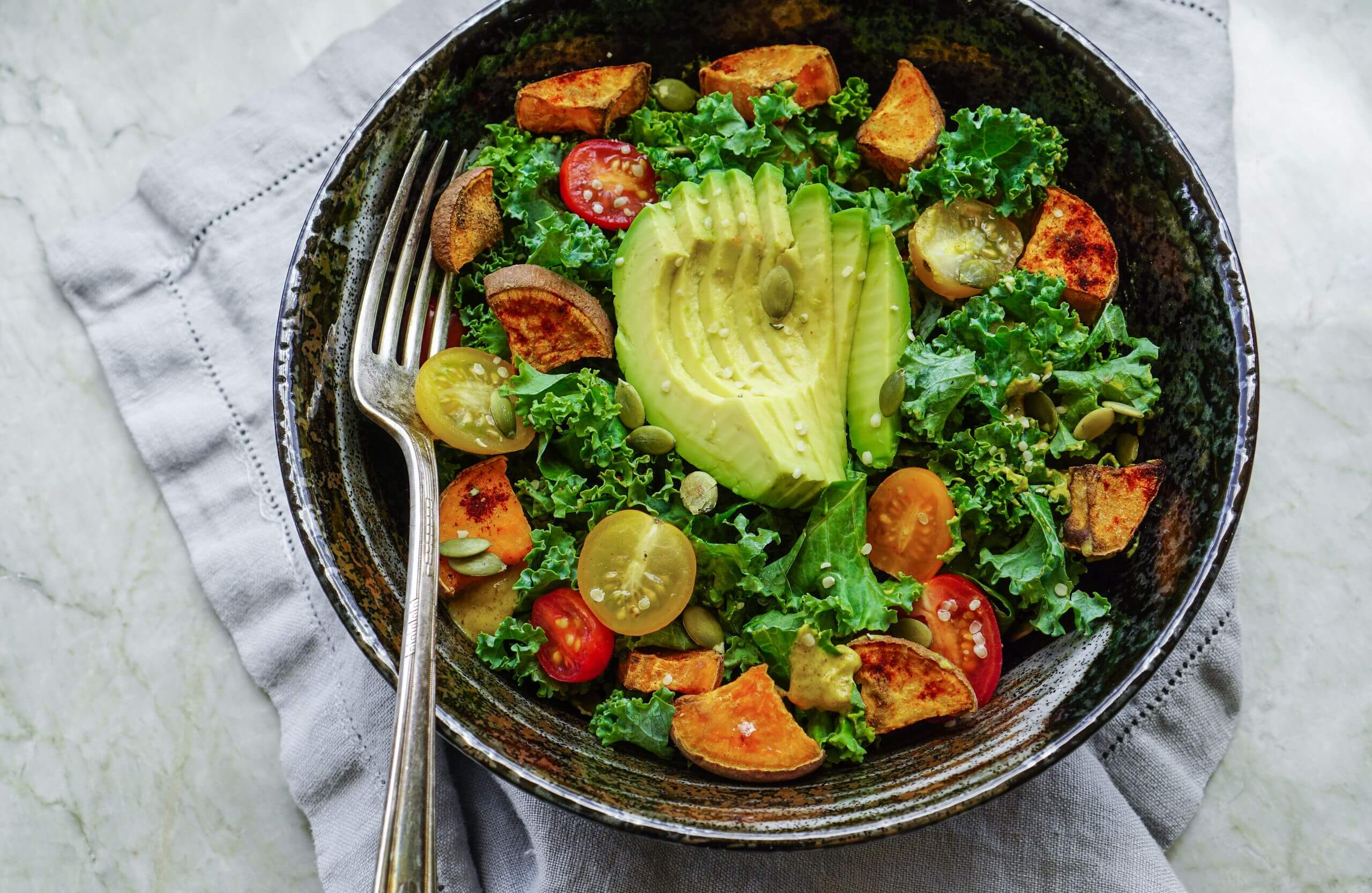 Kale, fried yams and avocado salad on a stone background