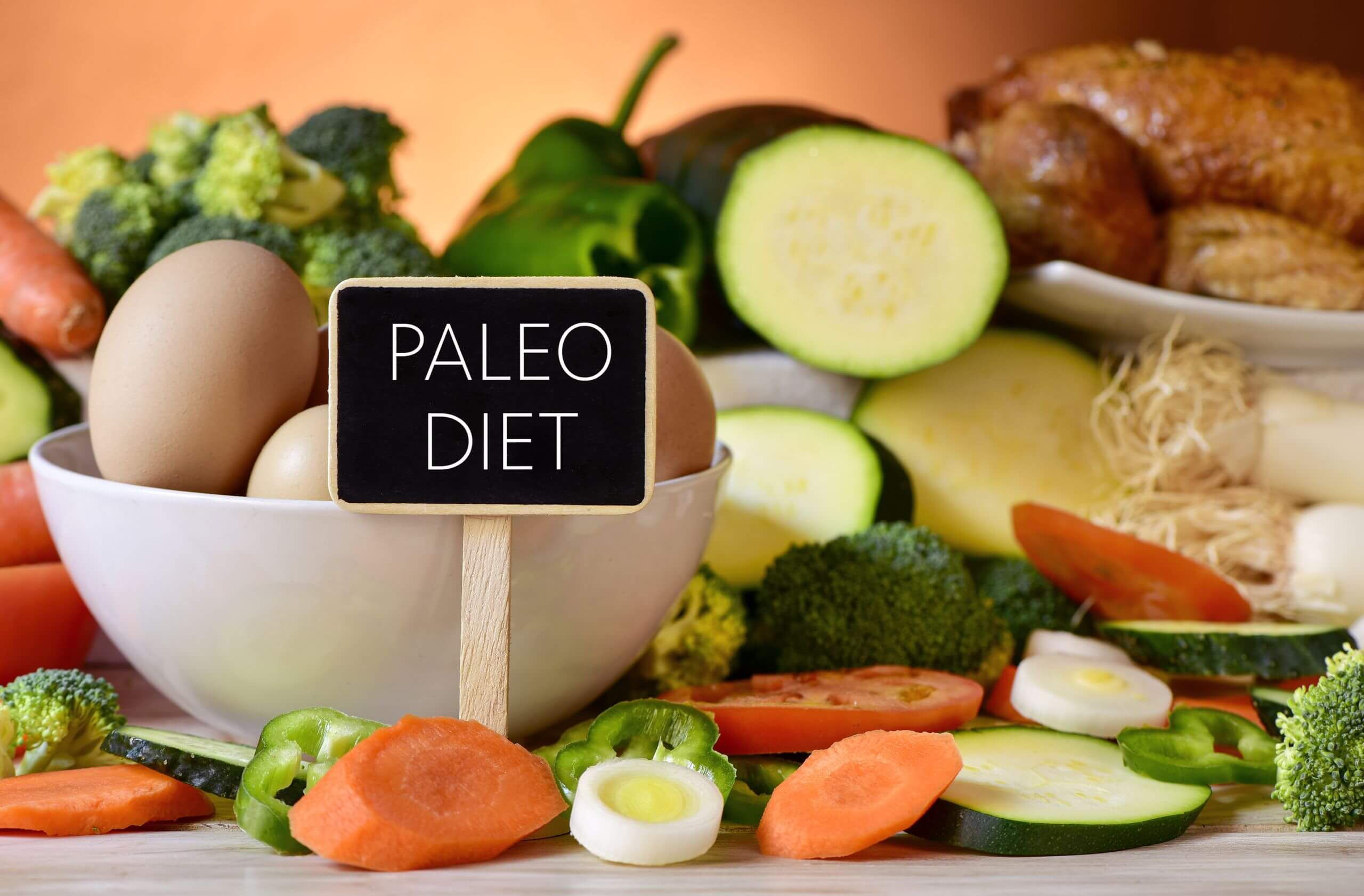 Paleo diet sign on a table full of various raw vegetables, a bowl of chicken eggs and chicken