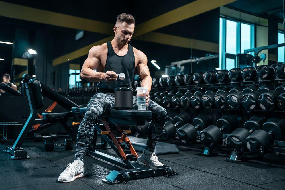 athlete man preparing protein cocktail or use sport nutrition supplement in gym