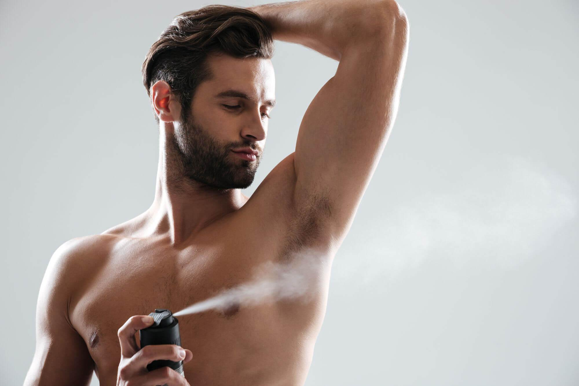 Young man using deodorant isolated